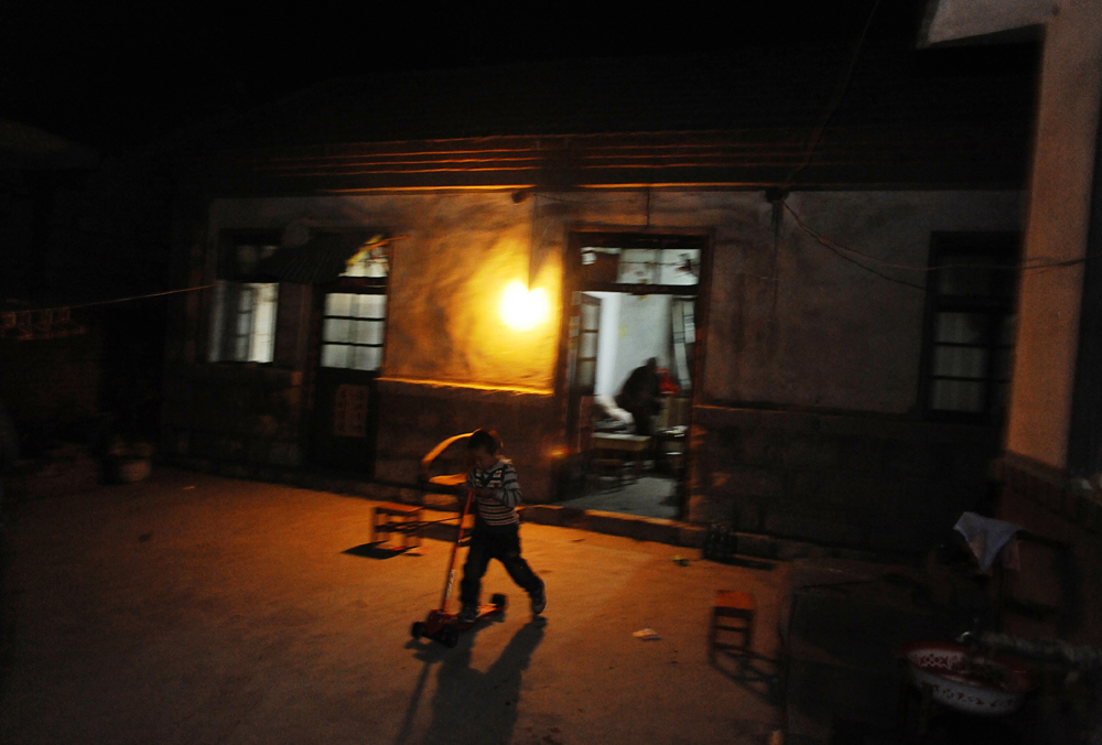Li Jia-yi (5) rides a tricycle around the courtyard of his house in the evening. Lin Yi-City, Shandong Province, China.
