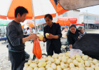 Li Chuan-hua purchases a couple of melons from a street vendor while his wife and son also looks over. Lin Yi-City, Shandong Province, China.