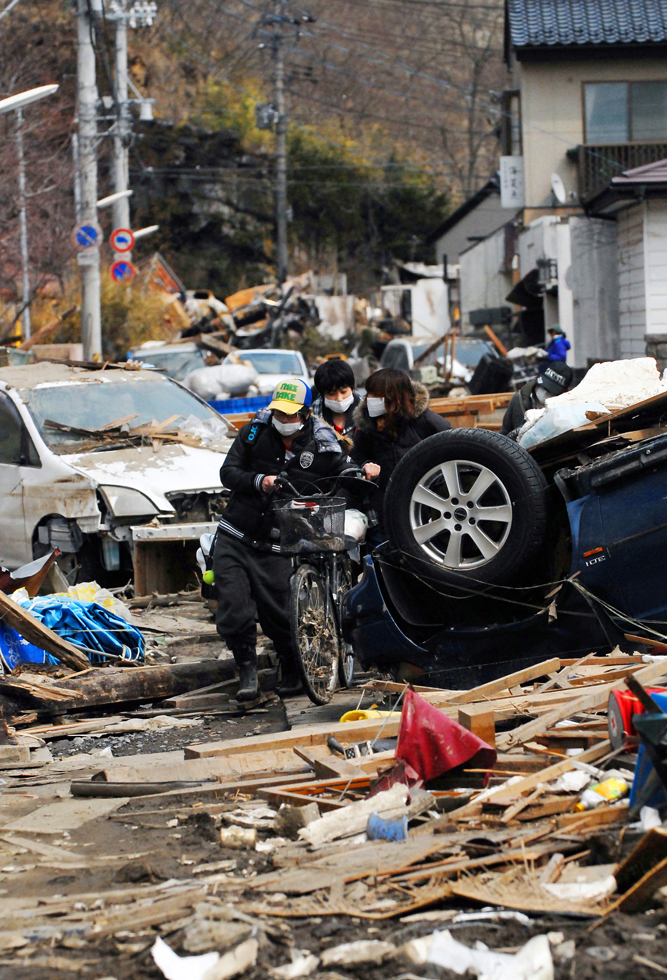 Residents push a bicycle in the rubble and ruins of the earthquake and tsunami.There was permanent fuel shortage in the quake/Tsunami hit area. Ishinomaki, Miyagi prefecture