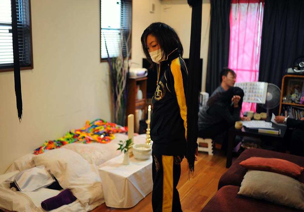 Takaki Hara's mother, Kuniko Hara (62) passed away after a long struggle with cancer on Feburary 2,2013. Rukiya Hara(13)  attends a wake of his grandmother somberly holding at their new home in the suburb of Kawasaki, Kanagawa prefecture. February 3, 2013.