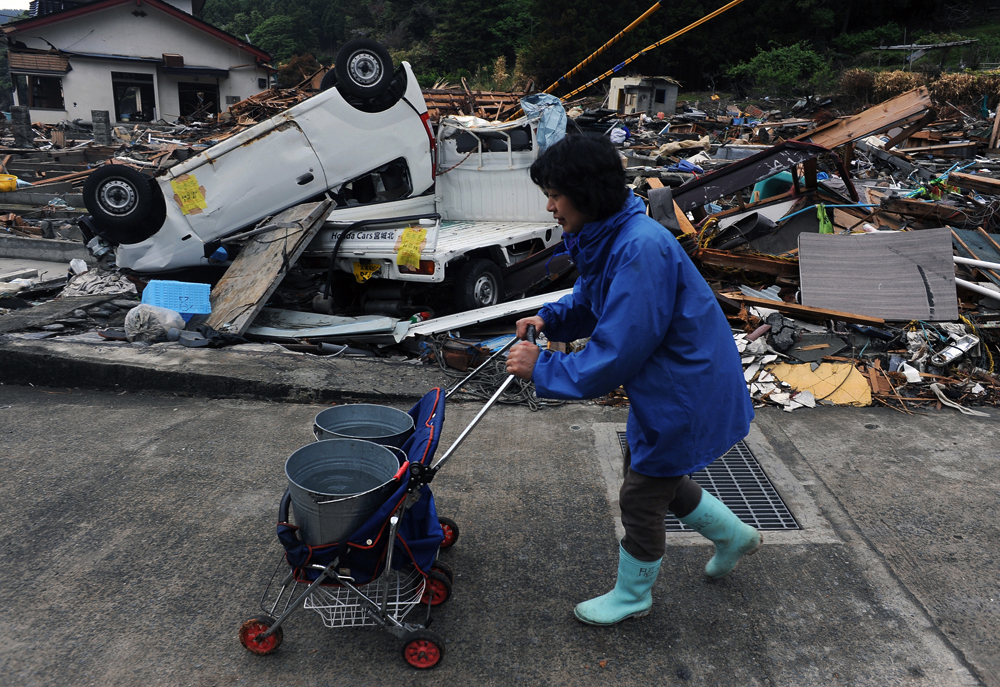 Akiko Kameyama (55)* delivers water for sewage disposal use to her neighbors among tsunami wreckage in Hamagurihama in Ishinomaki, Miyagi prefecture. She does it at least twice a day for her neighbors. {quote}I still can't  believe this actually happened,{quote}said she.*not related with  the previous {quote} Akiko{quote} Kameyama (59), using different Chinese character from the previous {quote} Akiko.{quote}