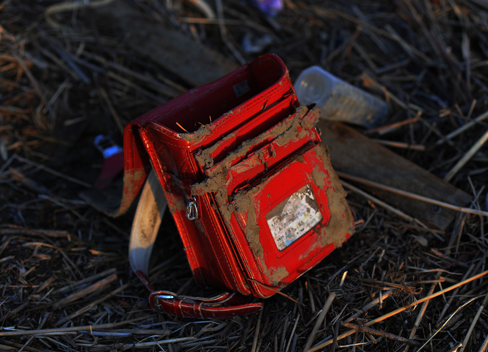 A girl's school backpack stranded on the shore of Natori river, Sendai, Miyagi prefecture.