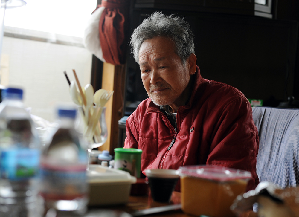 Seijii Hoshi (76) stays calm in a room on the second floor of his house with his wife at Ishinomaki, Miyagi prefecture. The first floor was destroyed by tsunami . His wife has a heart condition and can't evacuate to the nearby evacuation center.So he and his son take care of her although there have been no power,water, and gas for two weeks since the earthquake and tsunami hit the area.