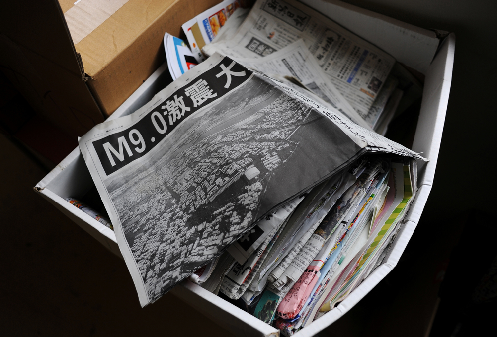 A stack of local newspapers at Minato elementary school evacuation center in Ishinomaki, Miyagi prefecture.