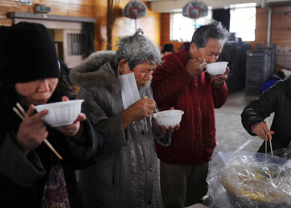 Tomi Hoshi (82),left and Seiji Hoshi(76),right  take emergency rations at the nearby evacuation center. It is the first time for them to venture out and have a hot meal because Tomi Hoshi has a heart condition and they stay in a room on the second floor of their home together.
