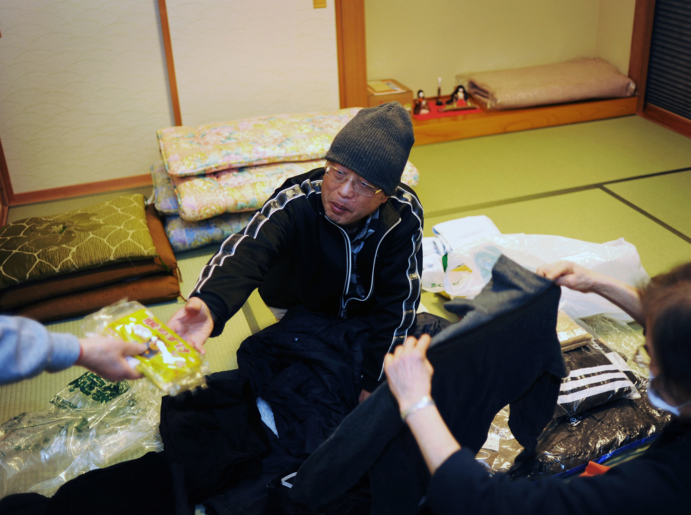 NPO volunteers hand out emergency rations such as clothes, food to  Shinji Endo(70) whose house in Minami-Soma near the Fukushima Daiichi nuclear plant was swept away in tsunami and lost everything, North Catholic church in Sendai, Miyagi prefecture. His family is okay.