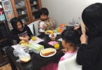 Rukiya Hara (12),far left,  eats their own self-cooked breakfast with Hibiki Murakami (9), right, also single father's child, while his sister, Sakurako Murakami (8) helps Hime Kumagai (5), a child of single mother, a member of Takaki Hara's single parent's NPO, to tidy up her hair. Rukiya and Takaki Hara sleep over at one of their single father friends, Yoshinobu Murakami (31)'s home in Sendai, Miyagi prefecture. They are on the way to the Tohoku region where the 3.11's M9 earthquake and Tsunami devastated as part of Takaki Hara's annual NPO and personal mission trip. March 11, 2012.