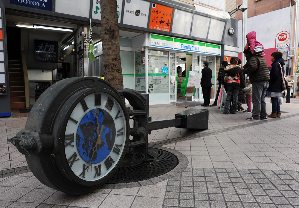 People of downtown Sendai form a line politely for shopping in front of convenience store beside fallen clock tower which stopped at a few minutes after the earthquake , 2.46.pm. There had been food,water and power shortages in Sendai, Miyagi since the earthquake.