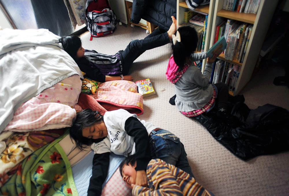 Rukiya Hara (12) wrestles with Hibiki Murakami (9), also single father's child while Sakurako Murakami(8) and Hime Kumagai (5),far right, a child of single mother, a member of Takaki Hara's single parent's NPO, playing alone in Murakamis' room.  Rukiya and Takaki Hara sleep over at one of their single father friends, Yoshinobu Murakami (31)'s home in Sendai, Miyagi prefecture. They are on the way to the Tohoku region where the 3.11's M9 earthquake and Tsunami devastated as Takaki Hara's annual NPO and personal mission trip.      March 11, 2012.