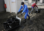 Volunteers from Sendai clear debris and mud from the parking lot after tsunami in Higashi-Matsushima, Miyagi prefecture.
