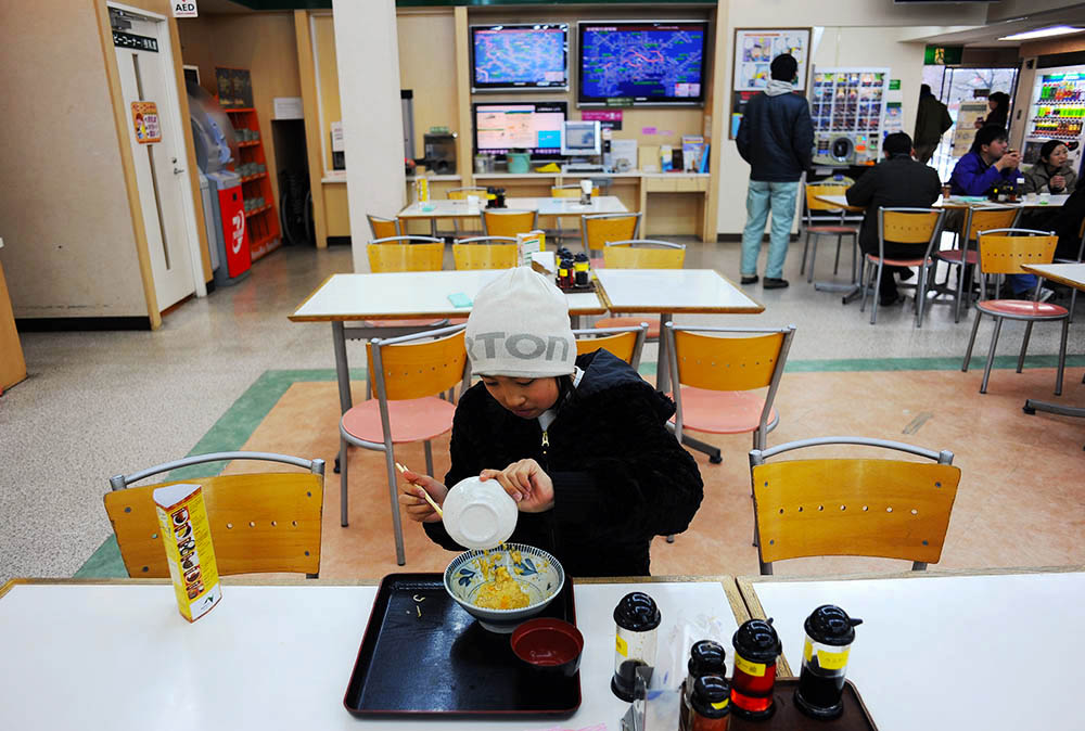 Rukiya Hara (12) finishes his lunch bowl at a gas station cafeteria. He and Takaki Hara are on the way back home from the Tohoku region where the 3.11's M9 earthquake and Tsunami devastated and they visited there as Takaki Hara's annual NPO and personal mission trip.  March 12, 2012.