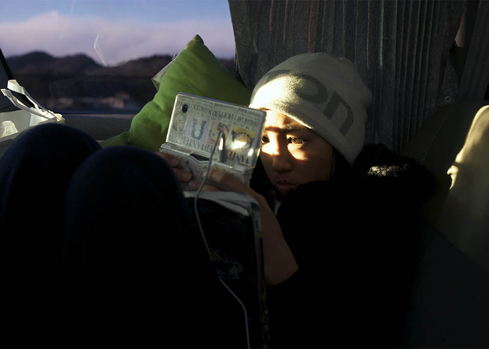 Rukiya Hara (12), is totally absorbed in Nintendo DS game in a backseat of mini-van. He and Takaki Hara are on the way back home from the Tohoku region where the 3.11's M9 earthquake and Tsunami devastated and they visited there as Takaki Hara's annual NPO and personal mission trip. March 12, 2012.