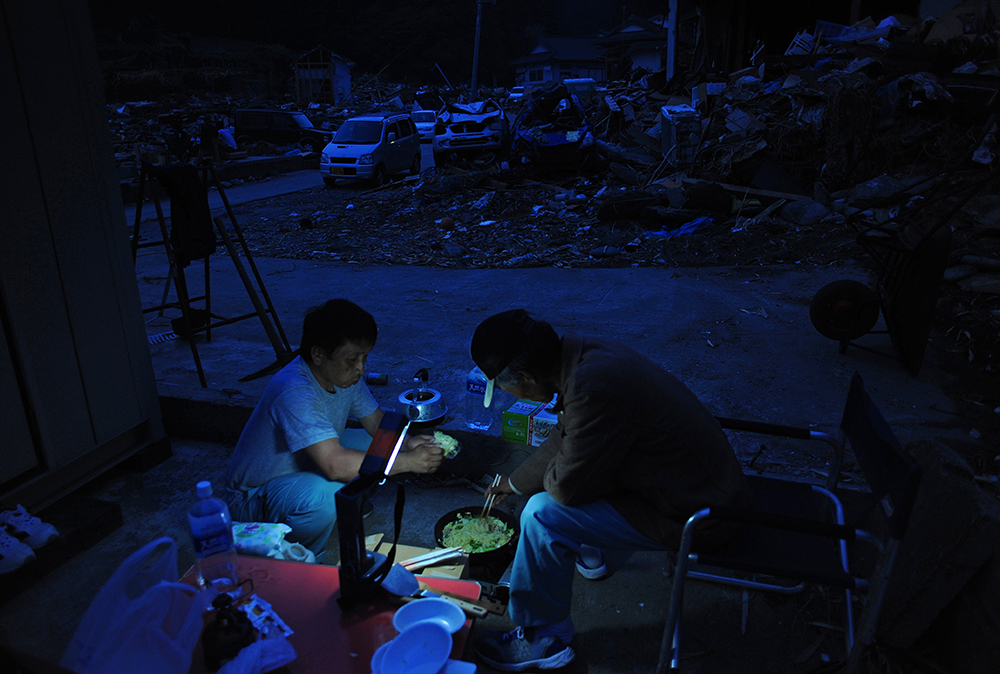 Volunteers form Tokyo cook instant chow mein at night among tsunami damaged wreckage Hamagurihama in Ishinomaki, Miyagi prefecture.