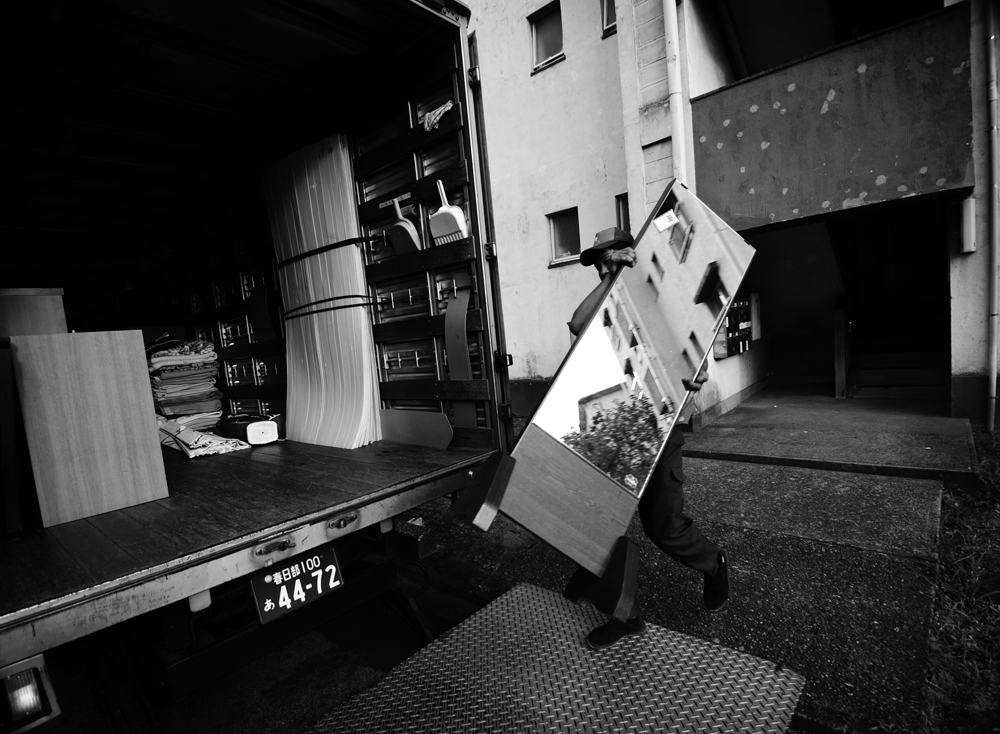 A Sakai moving company crew carries discarded furniture for a resident who is moving out.  More than 1000 units out of the Hanahata Danchi's 2725 units are unoccupied and the exodus of residents has no end in sight.                                                                                       2009/07/12