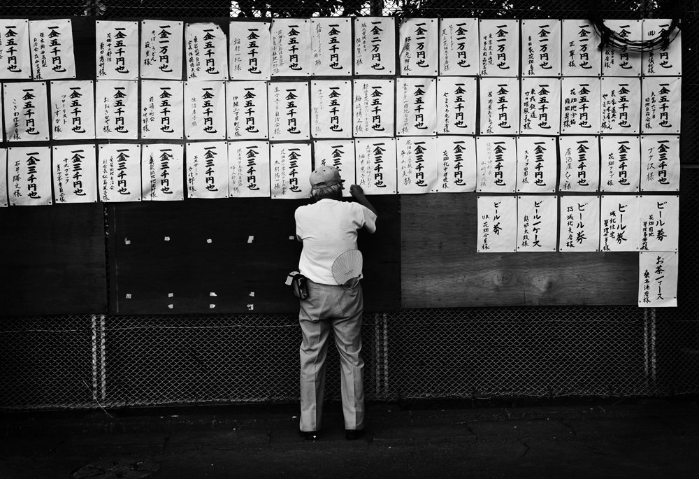 A member from the Hanahata Residents' Association pins up donation tabs for the annual Hanahata Danchi community's two-nights Summer Obon Dance festival at the park in front of Building #36.                                                                                2009/07/25