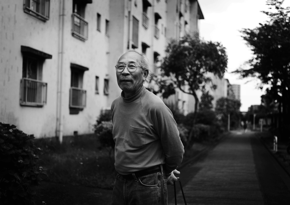 Kiyoshi Ueki, 77, always keeps his neighborhood clean. He has lived in the Hanahata Danchi for 40 years with his wife. He says, {quote}I am so happy to see my grandchild. It is one of my life's greatest pleasures right now.{quote}                                                                                     2009/05/16