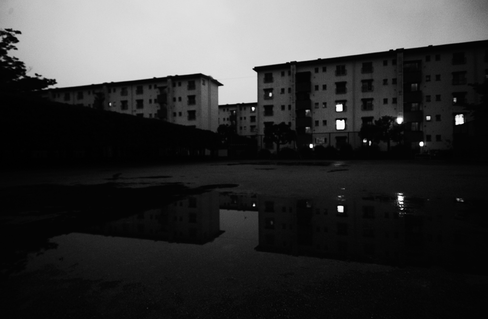 Building #29 and 30 of the Hanahata Danchi   (apartment complex), are reflected on a pool of the field on a Sunday evening.                                                                  2009/06/21