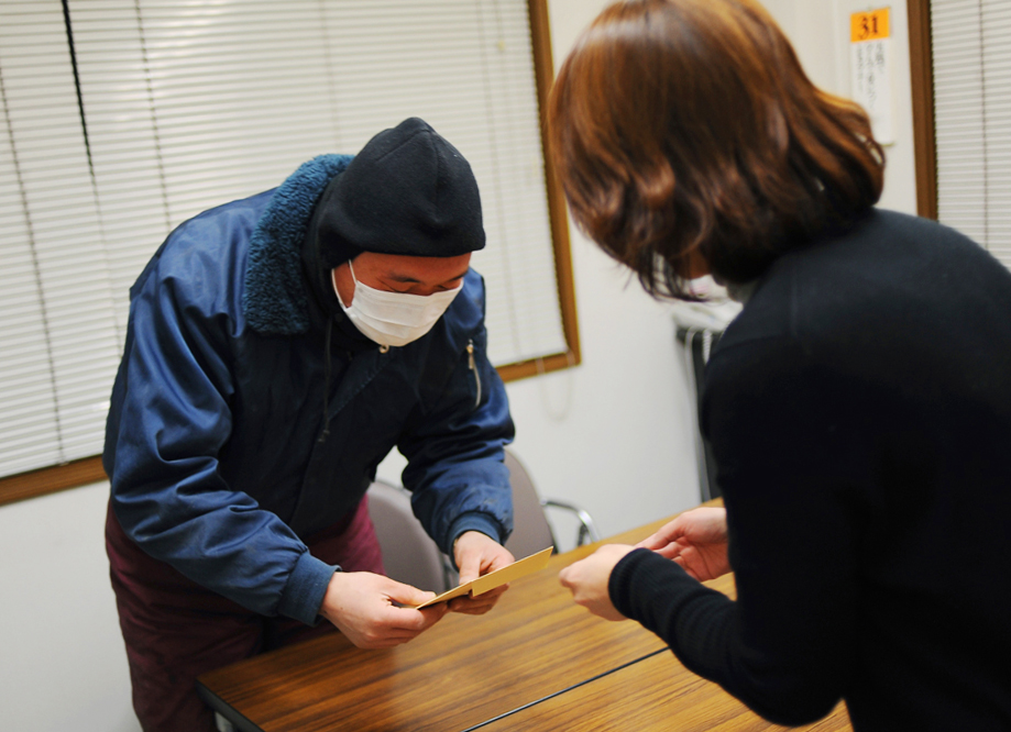 Li Chuan-hua receives monthly payments at the company's main office on the last day of every month. He wears a mask because he catches the flu.