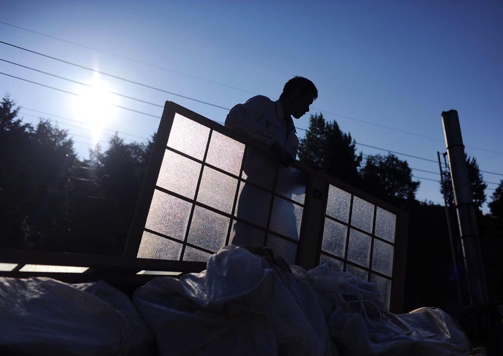 Li Chuan Hua works at a company's storage space in the early morning before he leaves for the assigned field. He and Su Li-li, both 20s, are the youngest workers in the company. The other Japanese workers are all above 40s.
