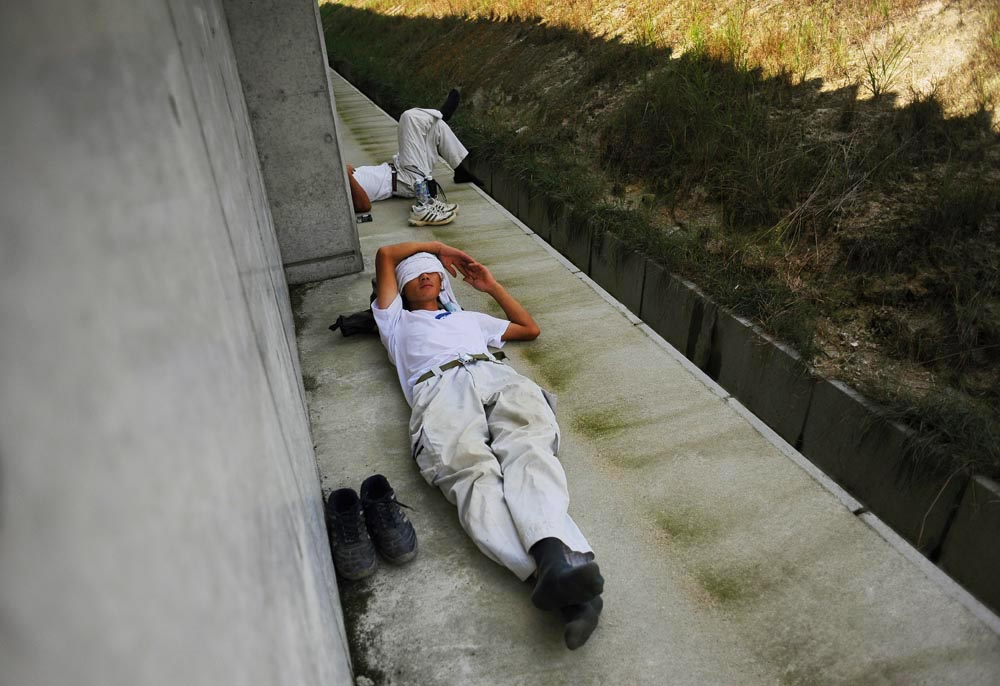 Li Chuan-hua takes a short nap after lunch, about  half an hour, with his supervisor of the day, Shusaku Terakado,40, in the shade near the assigned field on a sizzling summer day.