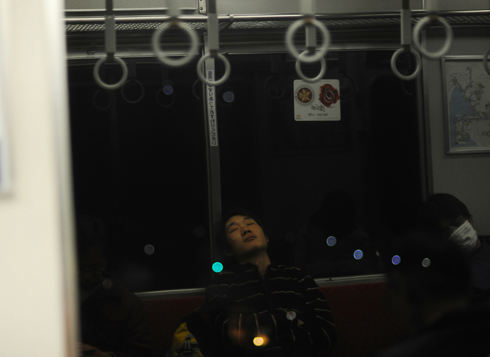 Li Chuan-hua, drowning in slumber after a tiring day of the Japanese Language Proficiency Test, is reflected on the window of the  train on his way back home.