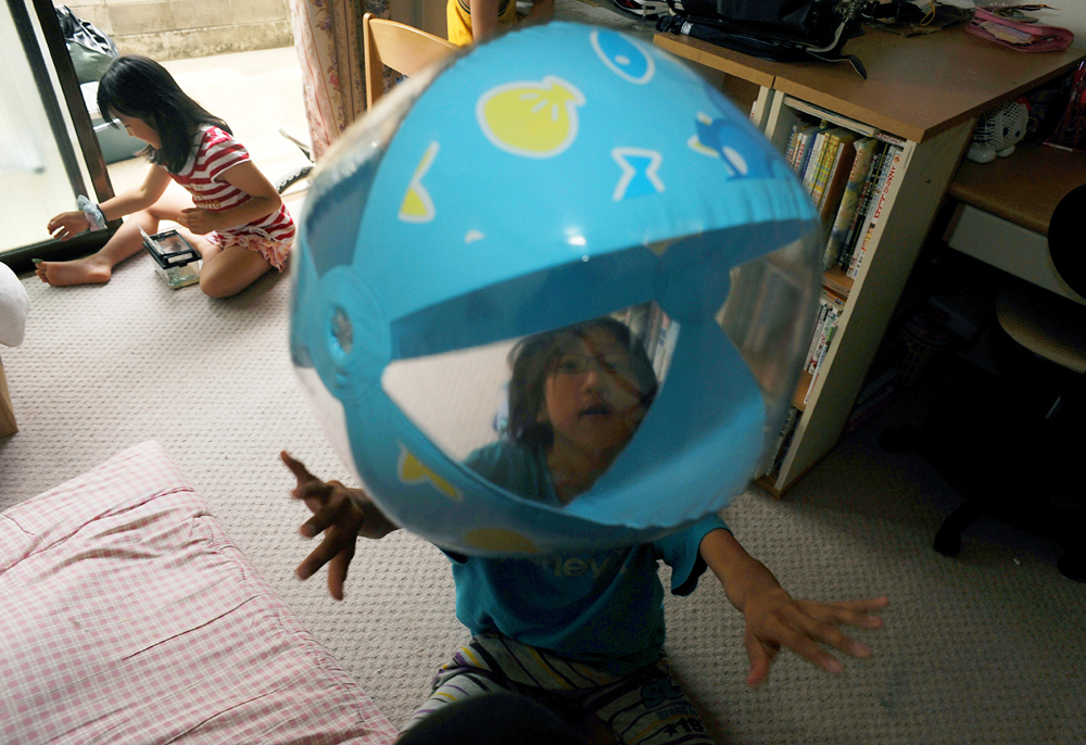 Rukiya Hara (12) plays with a beach ball while his friend, Sakurako Murakami (8), left, also single father's child, fondles with a pet frog in Sakurako's room. Rukiya and Takaki Hara sleeps over at one of their single father friends, Yoshinobu Murakami (31)'s home in Sendai, Miyagi prefecture on the way to the Tohoku region where the 3.11's M9 earthquake and Tsunami devastated for volunteering and research on the newly displaced single parent families due to the 3.11 earthquake as part of Takaki Hara's NPO and personal mission. June 12, 2011.