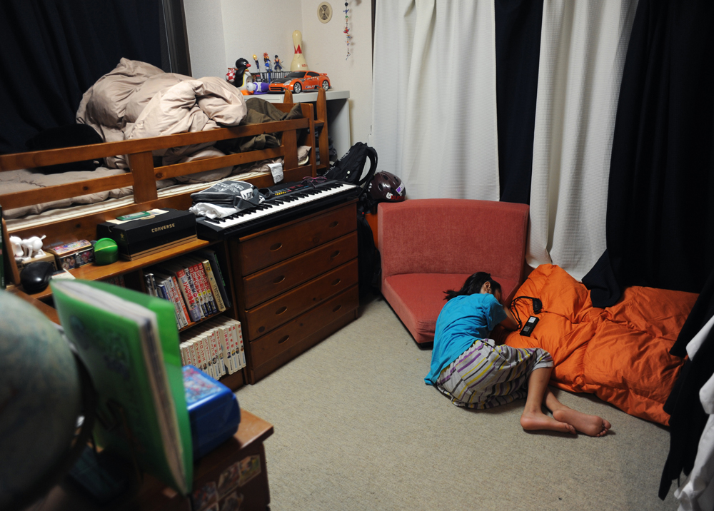 Rukiya Hara (12) falls into a deep sleep on chair cushion with his iPod in his room on Saturday night.  Kawasaki-city, Kanagawa prefecture. June 11, 2011.