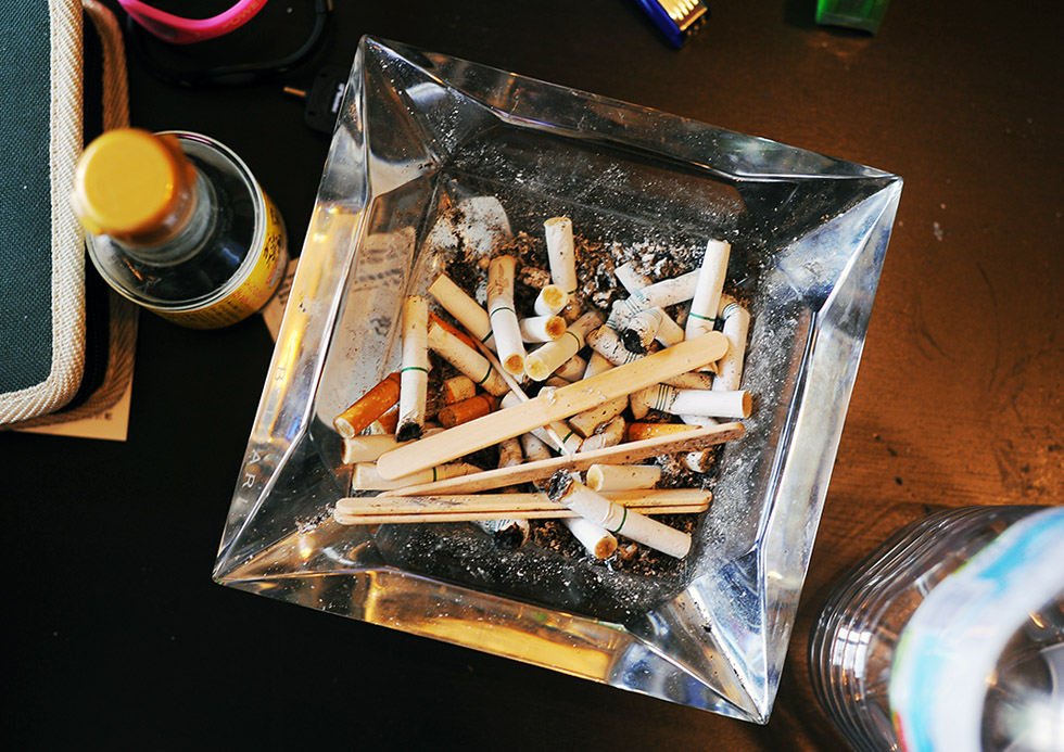 Takaki Hara (38)'s cigarette butts and popsicle sticks accumulated in an ashtry. Kawasaki-city, Kanagawa prefecture.  August 13, 2011.