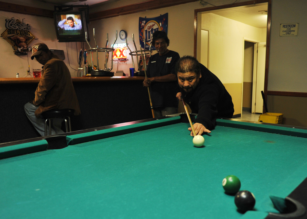 Almendo Ballesteros, owner of Ballesteros Mexican Restaurant, plays billiards with Rudy Zarate, employee of the restaurant at his own Ballesteros' restaurant with closing time approaching which is 8 o'clock p.m..