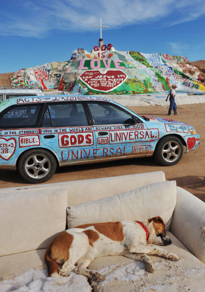 Salvation Mountain in Slab City, Niland, 2 miles southeast of the Salton Sea with Leonard Knight's dog. It is an epic colorful art installation which conveys the message that {quote}God Loves Everyone.{quote}  The mountain has become a kind of piligrimage site. As many as 50 people a day visit this site.  In 2002, Salvation Mountain was placed under protection when California Senator Barbara Boxer entered it into the Congressional Record as a national treasure.