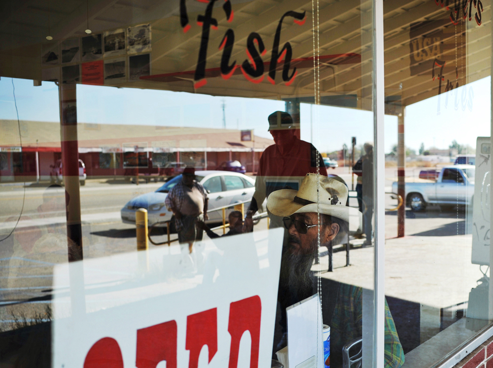 People hanging around the Post Office are reflected on the window of Bobby D's Pizza Plus in Niland.