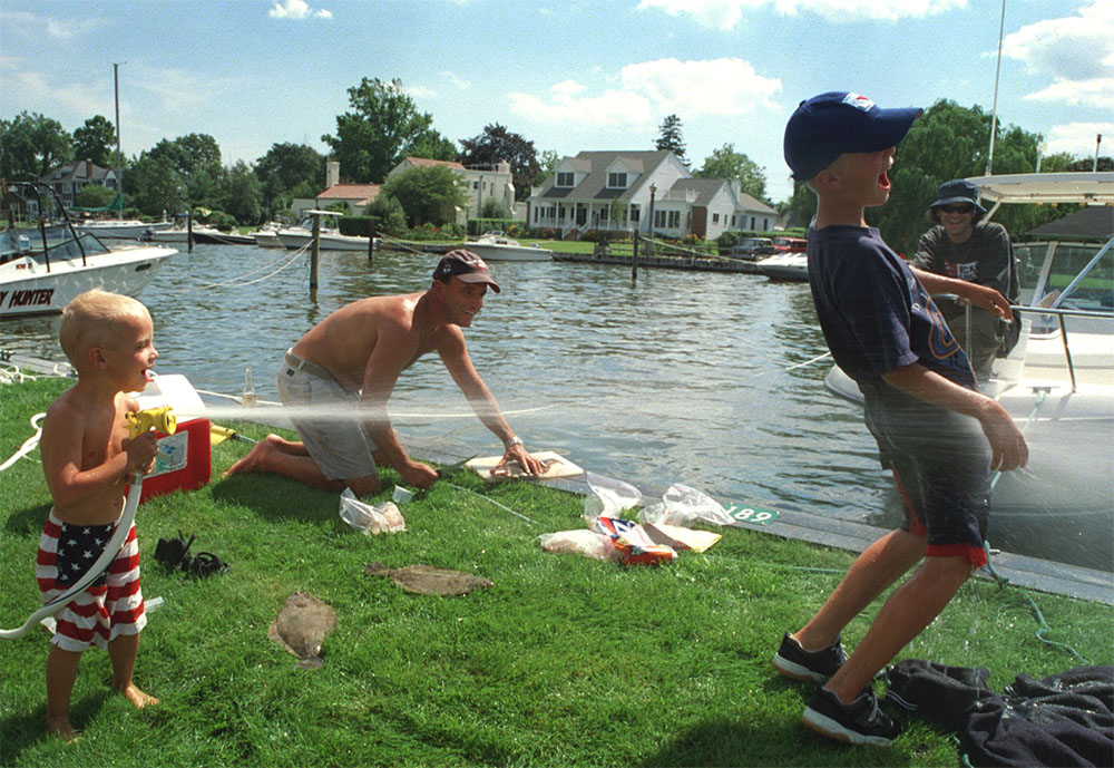 Sean Collins,3, splashes water on Ryan Collins,9, while their father, Doug Collins ,33, slices up flatfish in  Bay Shore, NY. The oldest brother, Kenney Collins (with hat and sunglasses) looks over.  (c) Newsday