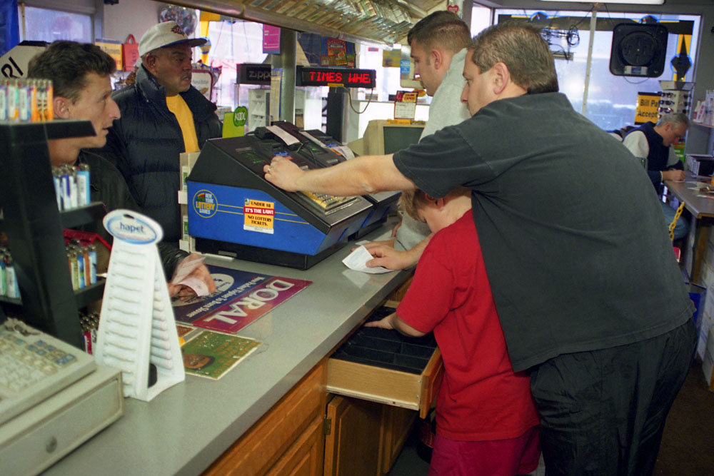 Matthew Fantacone,8, center, gives a hand to his father,Robert Fantacone. Corey Fuller,23, also at cash register.