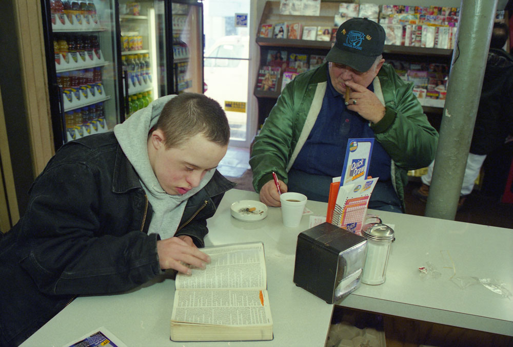 Chad Cooper,16, who has Down Syndrome,reads the Bible while Fred Ranger,60, playsQuick Draw.