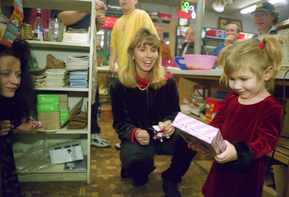 Roxane Crosby,left, cashier, and Shawn Fantacone celebrate Christmas Eve with excited Jennifer Fantacone,2,at the annual Chase's Christmas Eve party.
