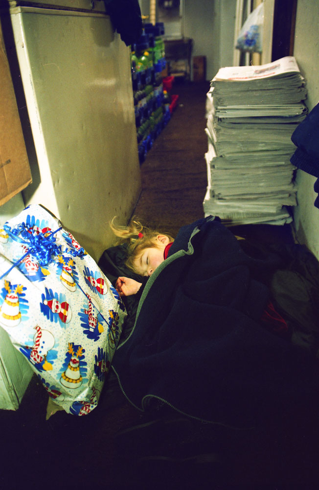 Jennifer Fantacone,2, takes a nap next to a Christmas present in the storage room at the Chase's.