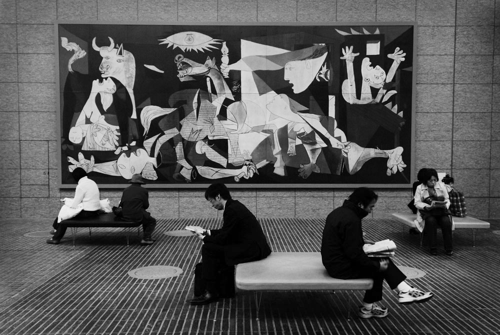 A group of strangers are absorbed in reading in front of the ceramic reproduction of Picasso's 'Guernica' at Tokyo's Marunouchi Oazo center's public square on the afternoon of November. The ceramic reproduction was produced by Otsuka Ohmi Ceramics Co.,Ltd. True to the original, the company's technology succeeds in reproducing the original color and texture which can be preserved for more than 2000 years.