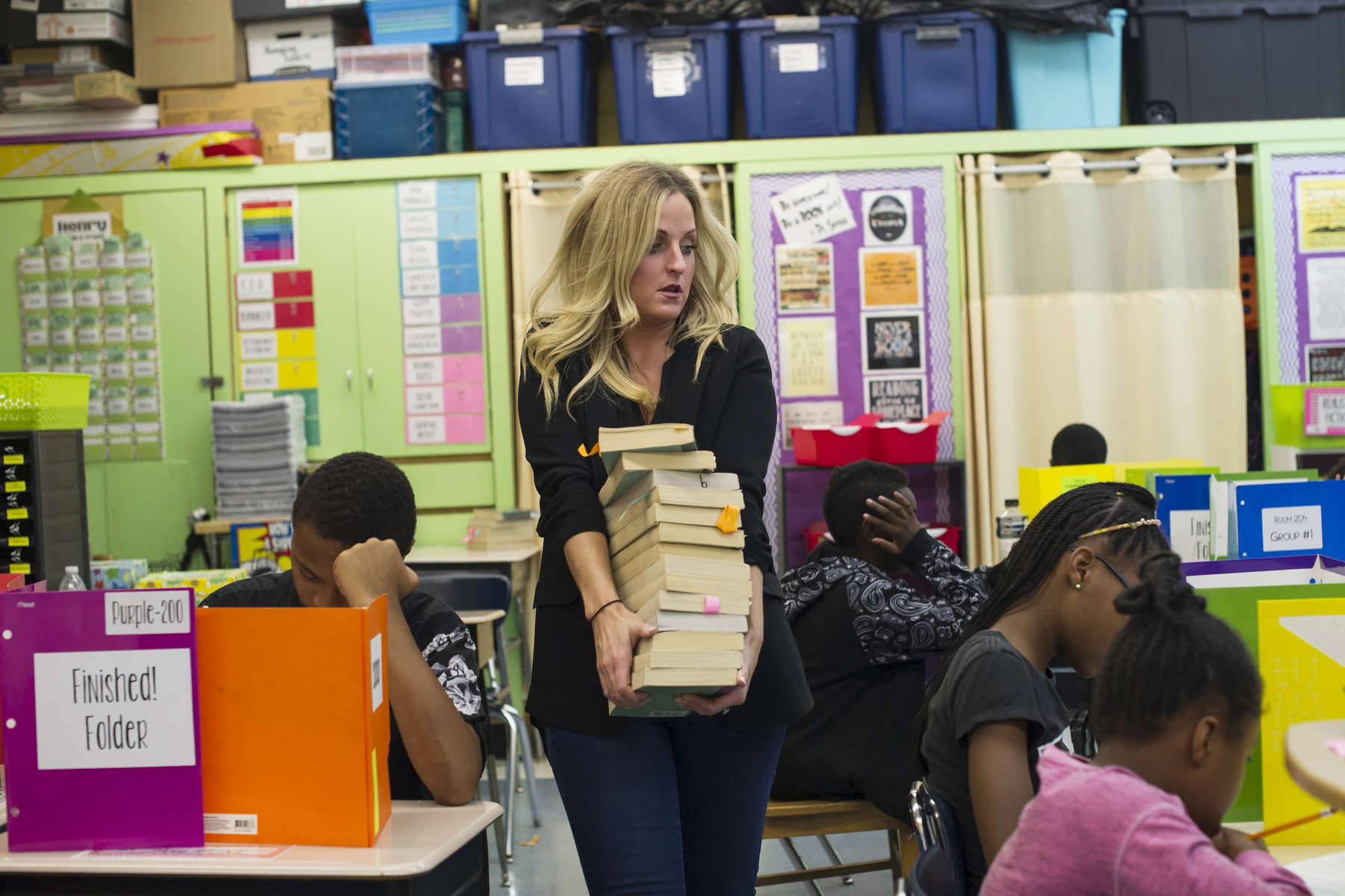 Sixth grade teacher Erin Henry carries books to be distributed for open reading as her students take a vocabulary quiz at Beulah Shoesmith Elementary School, October 7, 2016.