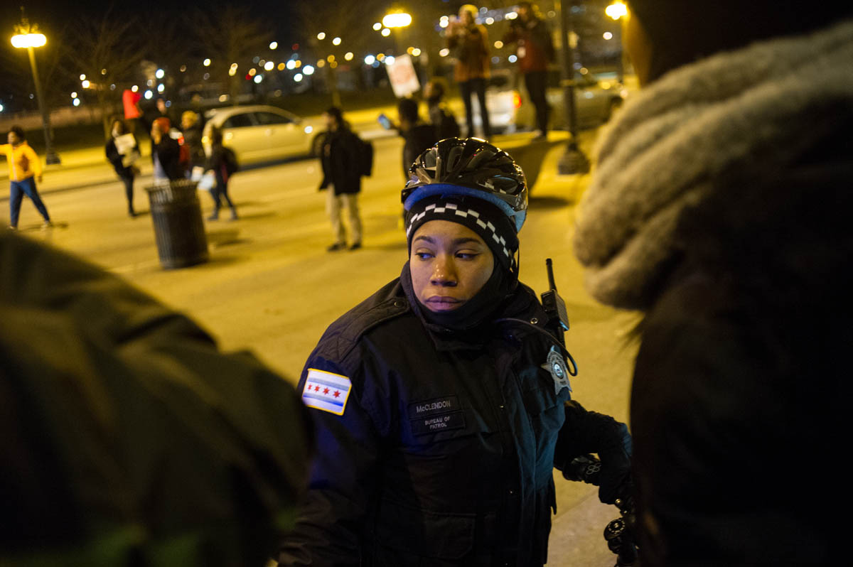 A City of Chicago Police woman faces protestors who are attempting to move onto and block Chicago's Michigan Avenue during demonstrations against the killing of Michael Brown in Ferguson, Missouri.