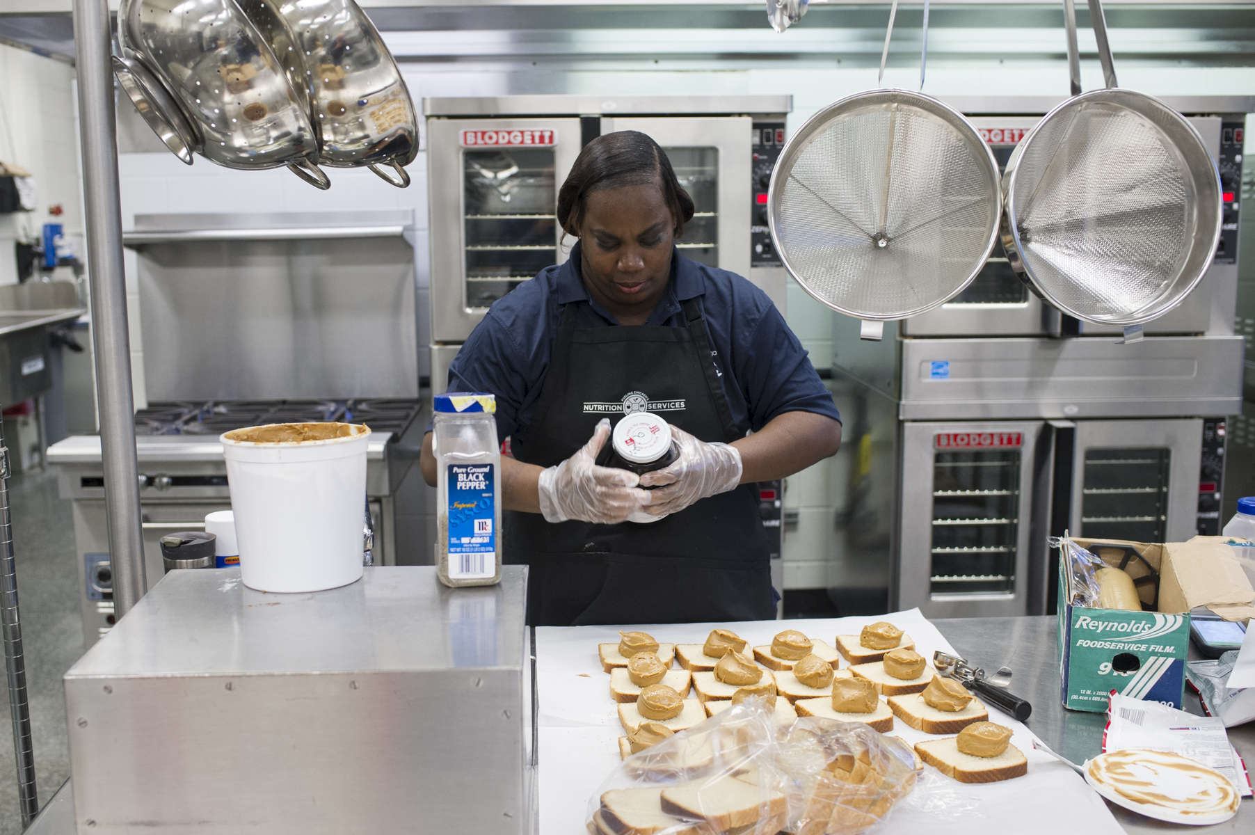 School cook Chandra Kilgore prepares peanut butter and jelly sandwiches in the school kitchen at Dyett High School for the Arts, October 31, 2016.