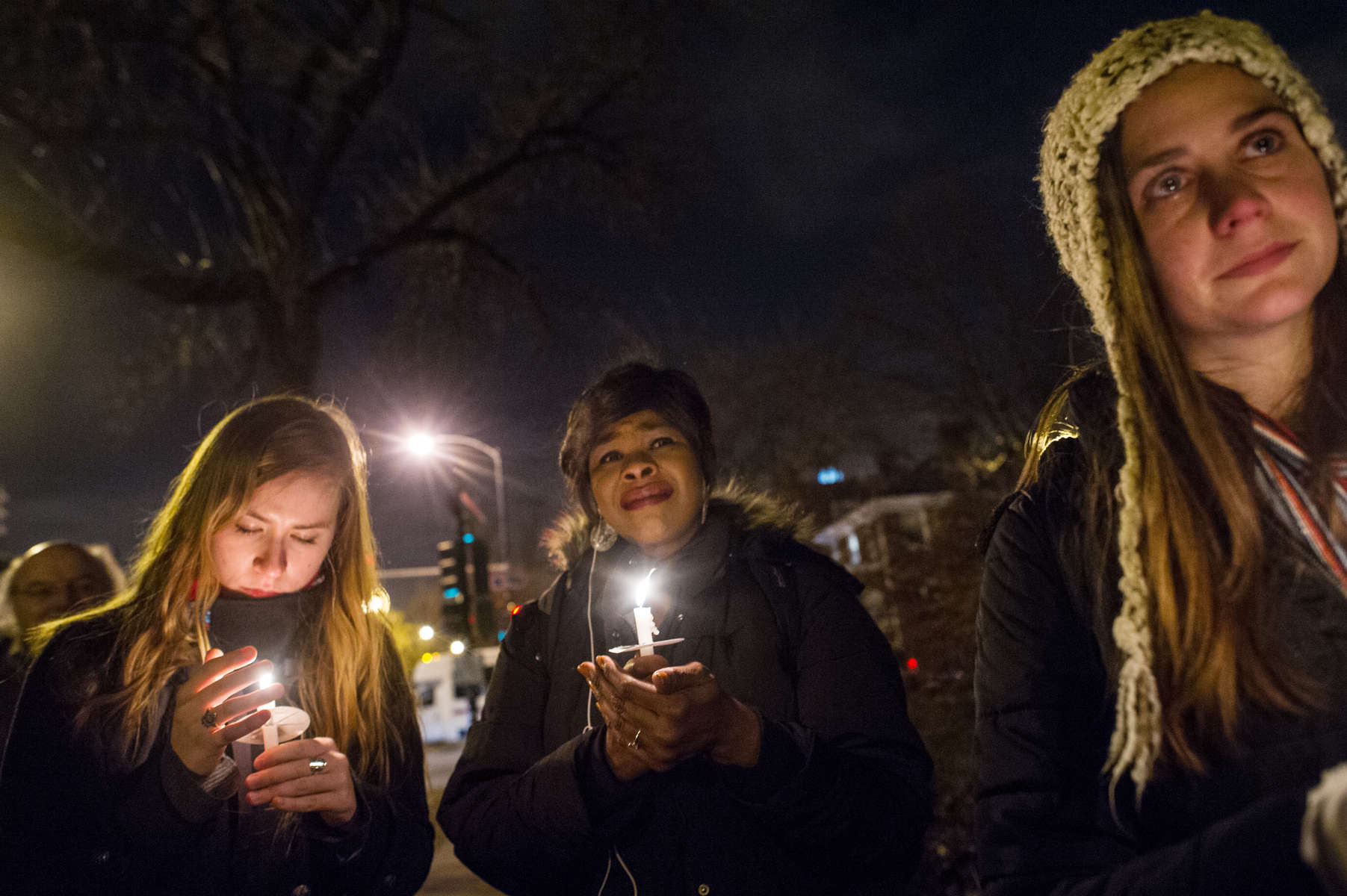 Women participate in a vigil at The First Unitarian Church of Chicago marking the shooting of Michael Brown in Ferguson, Missouri.