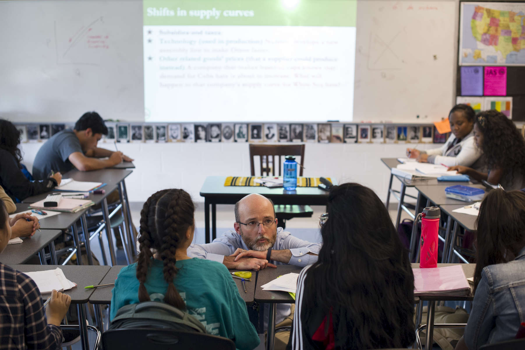 History teacher and college counselor Andrew Johnson speaks with students in his Economics class during a lesson on supply, demand and price relationships at George Westinghouse College Prep, October 6, 2016.