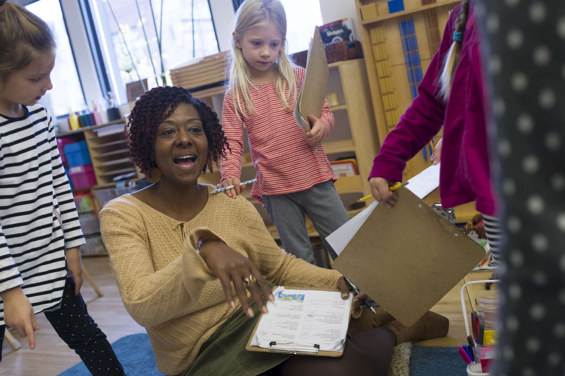 Classroom co-teacher Carmenita Peoples works with several of her students on their work plans in the mixed age class of 6 year-olds to 9 year-olds at the Montessori Academy of Chicago, October 20, 2016.