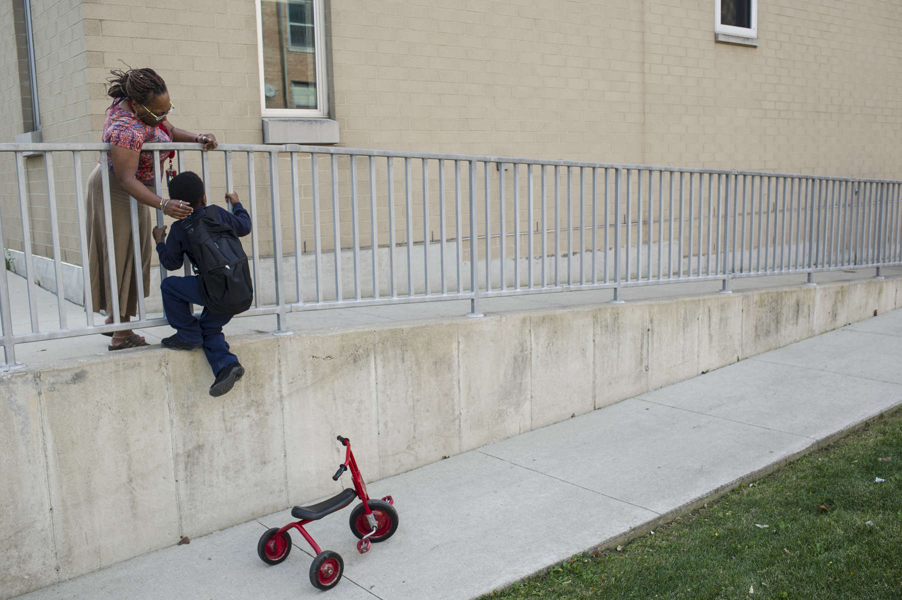 Special Needs classroom teacher Tammie Vinson helps a student as he climbs a wall during recess at Oscar DePriest Elementary School, October 18, 2016.