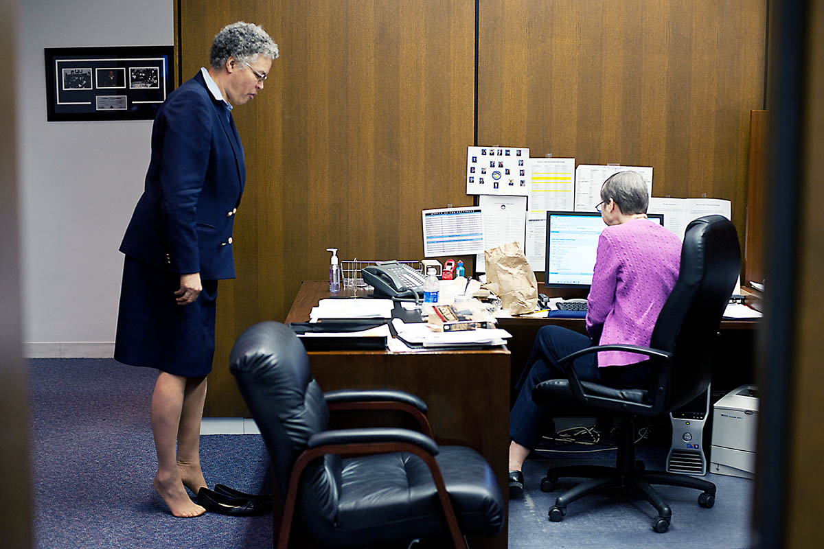 Cook County Board president Toni Preckwinkle does some toe lifts as she speaks to her long-time administrative assitant in her office.