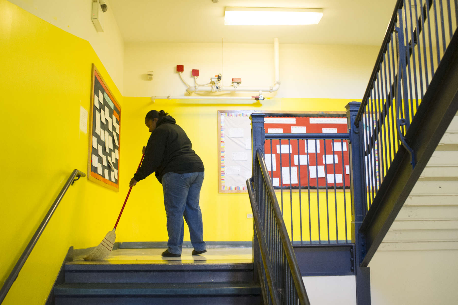 Custodian Sirena Buchanan sweeps a landing on a staircase of the University of Chicago Charter Schools North Kenwood Oakland Campus, November 16, 2016.