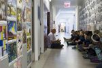 Lower school Art teacher Philip Matsikas meets fifth grade students in the hallway-gallery to start their fine arts class as he goes over the work plan for the day at the University of Chicago Laboratory Schools, November 9, 2016.