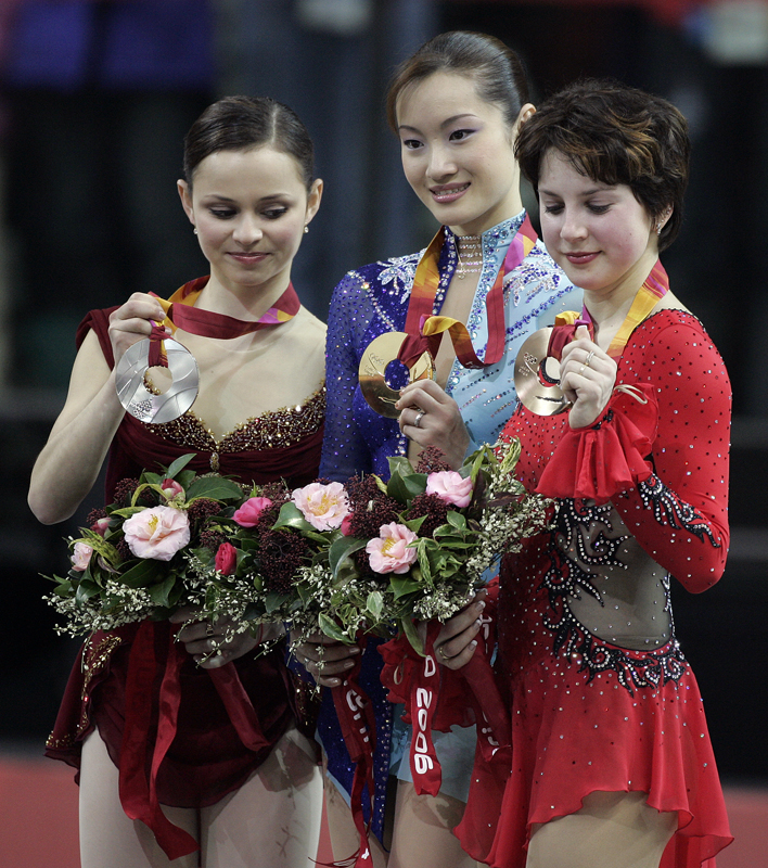 Figure skating medalists Sasha Cohen, of the USA, Shizuka Arakaw, of Japan, and Irina Slutskaya, of Russia, together on the medals stand following the ladies' free skating program at the 2006 Winter Olympics in Turin, Italy.