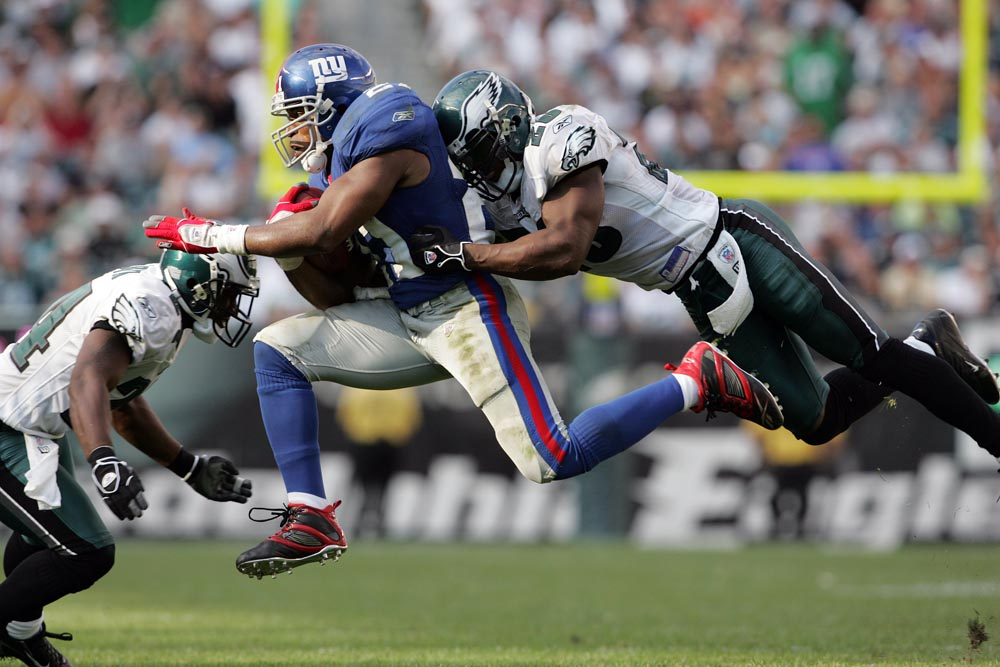 Philadelphia Eagles' Brian Dawkins (right) tackles the Giants' Tiki Barber in overtime. Assisting Dawkins on the tackle is Sheldon Brown.