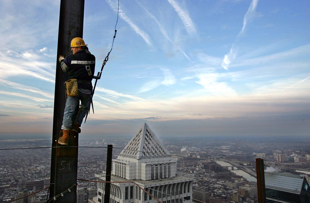 Almost 800 feet above street level, an ironworker waits for the crane to deliver a beam.